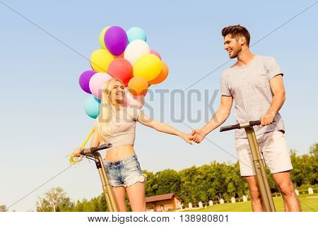 Happy Lovely Couple  With Balloons Holding Hands And Using Segway