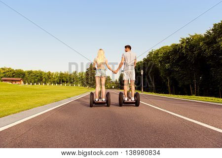 Back View Of Man And Woman Holding Hands And Riding Segway
