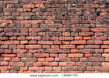 old wall of red and orange bricks for texture or background