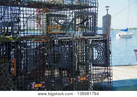 Lobster traps stacked on new England pier with nautical background