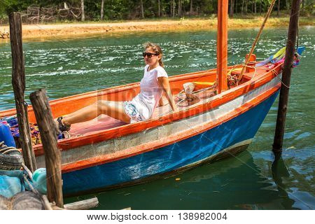 Young girl tourist sitting in a Thai fishing boat.