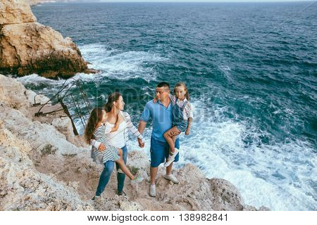 Family walking on the sea shore in sunset, travel photo series