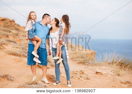 Family walking on the sea shore in sunset, parents kissing