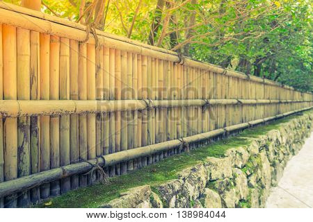 Bamboo fence on stone with green leaves ( Filtered image processed vintage effect. )