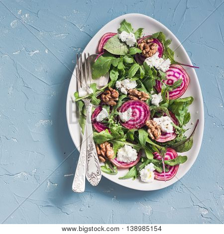 Salad with beets arugula feta cheese and walnuts. On a blue background top view