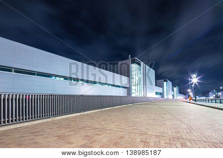 modern business building in downtown of tokyo at night on view from empty sidewalk