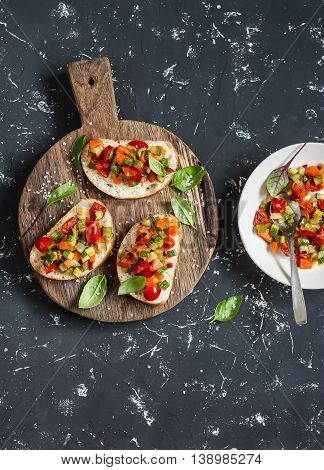Sandwiches with quick ratatouille on rustic cutting board on a dark background. Delicious healthy vegetarian food. Top view