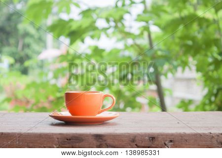 Mini orange coffee cup on tabletop with blurred green leaves background