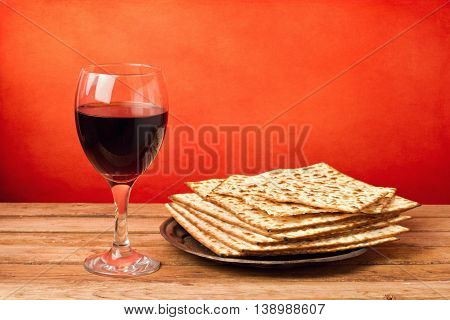 Glass of red wine and matza on wooden table over grunge red background