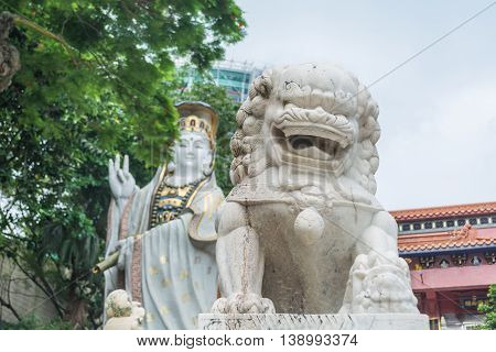 REPULSE BAY HONG KONG - MAY 23: The celestial lion statue and Kwun Yam statue at Kwun Yam temple on May 23 2016 in Repulse Bay Hong Kong.
