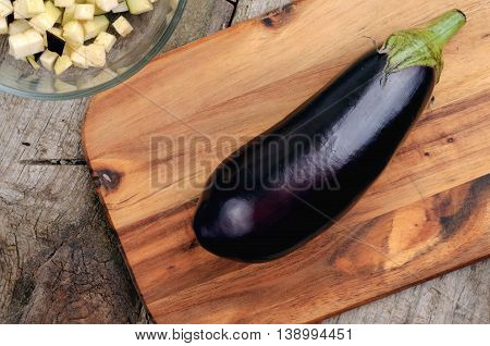 Purple eggplant on wooden table close up top view