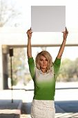 Transgender female in green sweater holding up a blank poster board sign for advocation messages. poster