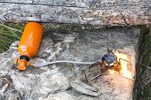 portable gas burner on the wooden logs. camping equipment poster