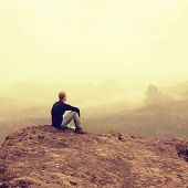 Tourist sit on peak of sandstone rock and watching into colorful mist and fog in morning valley. Sad man. Man sit. Man in jeans.Fall mountain mist. Mist in valleys. Man hand.Sad tourist sit in mist. poster
