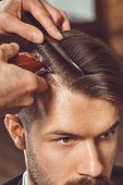 The hands of young barber making haircut of attractive bearded man in barbershop poster