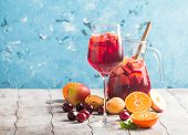 Refreshing sangria or punch with fruits in glass and pincher poster
