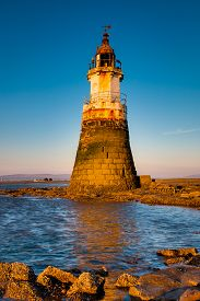 Plover Scar lighthouse at Cockerham on Morecambe Bay, Lancashire, UK. At sunset.