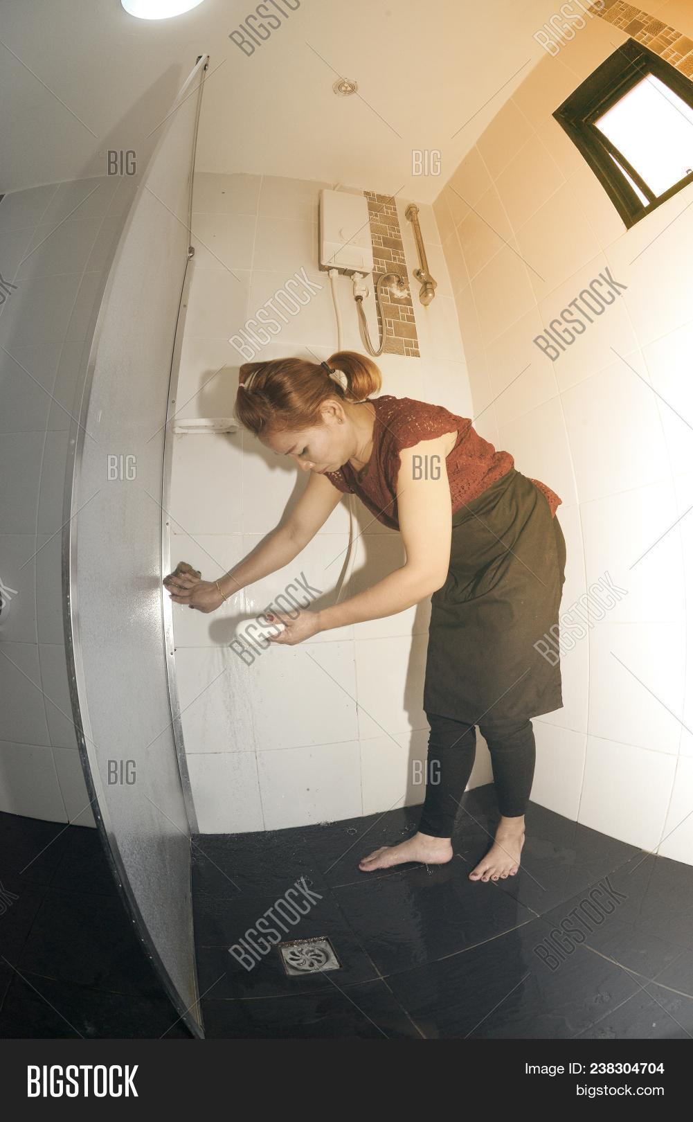 Asian Female Maid Or Housekeeper Cleaning Spray From Water Heater On A  Toilet Partitions In Bathroom