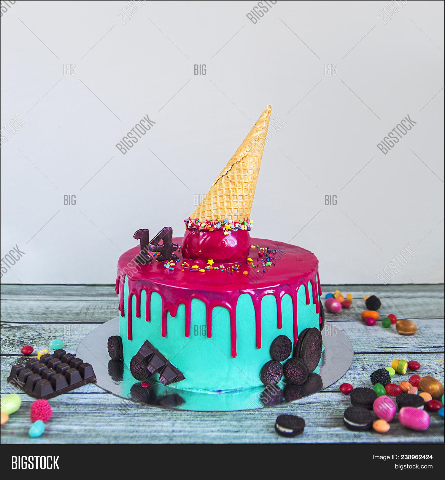 Birthday Cake With Pink Turquoise Coated Ice Cream Horn And Candies On A Wooden Table