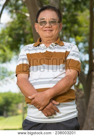 Portrait Of Cheerful Aged Man In Glasses Smilng And Looking At Camera