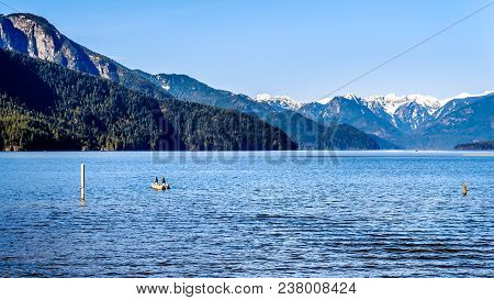 Fishing On Pitt Lake With The Snow Capped Peaks Of The Golden Ears, Tingle Peak And Other Mountain P