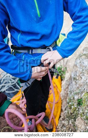 A Rock Climber Tie A Knot For Insurance.