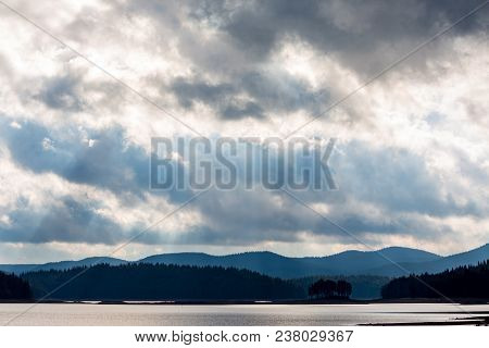 Silhouette of small natural island with pine trees and layered mountain hills background. Moody colorful image with overwhelming blue color at Shiroka Polyana lake, Bulgaria, Rhodope mountain poster