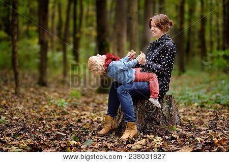 Little Boy With His Young Mother Having Fun During Stroll In The Forest. Active Family Time On Natur