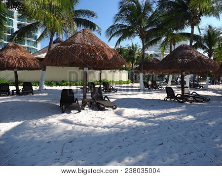 Sunbath Places Under Umbrella And Palm Trees On Tropical Sandy Beach At Cancun City Of Quintana Roo,