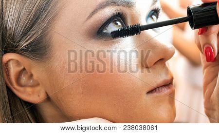 Closeup Of Makeup Artist Applying Mascara On Eyelashes