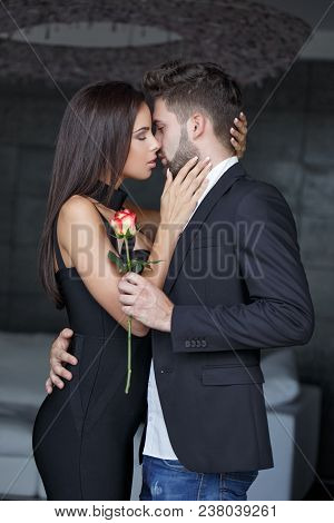 Young Rich Woman In Love Kissing Man With Rose, Indoors