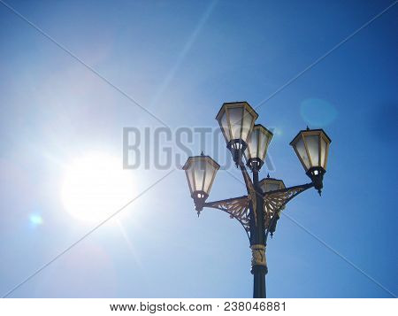 Lamppost Isolated On Empty Blue Sky Background. Vintage Old Street Lantern With Decorative Golden Or