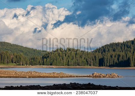 Scenery sunny lake landscape from Shiroka Polyana, Rhodope mountain, Bulgaria with puffy clouds, pine tree forest and brown stones on the shore poster