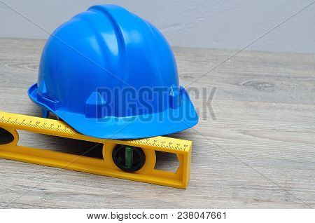 A Blue Hard Hat And A Yellow Level