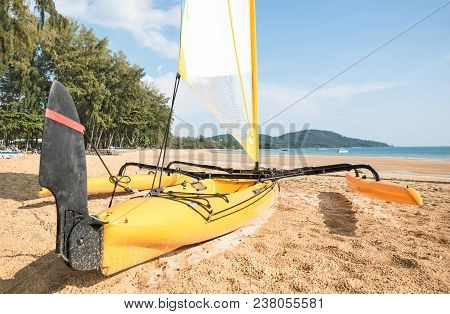 Small Catamaran Sailboat On The Shore - Water Sport Race Concept With Technical Equipment At Beach -