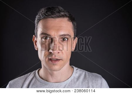 Handsome Face. Portrait Of A Nice Pleasant Young Man Standing In Front Of The Black Background While
