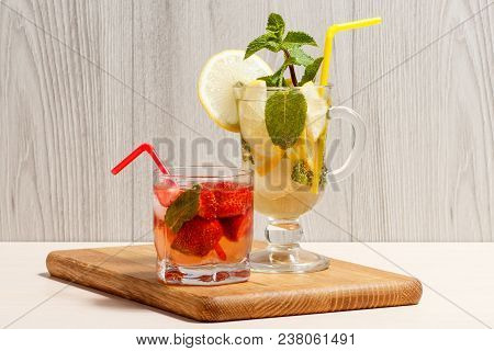 Cold Refreshing Summer Lemonade Mojito With Lemon Slices And Mint In A Tall Glass And Strawberry Lem