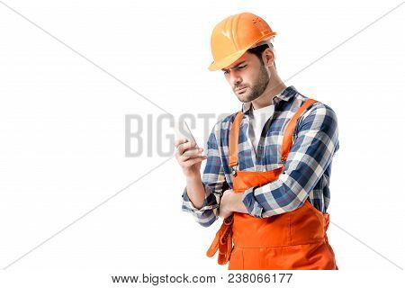 workman in orange overall and hard hat using smartphone isolated on white poster