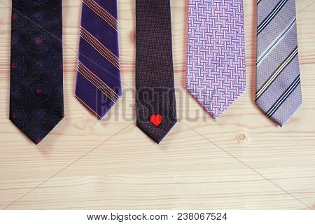 Five Violet Purple Neck Ties With One Little Red Heart On Light Natural Wood Background With Copy Sp