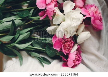 Lovely Pink Peonies On Legs Of Boho Girl In White Bohemian Dress, Top View. Space For Text. Stylish