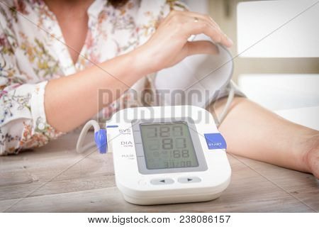 Women's hand with blood pressure monitor cuff. Checking blood pressure at home concept