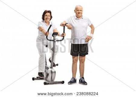 Mature woman on a stationary bike with a mature man leaning on it isolated on white background