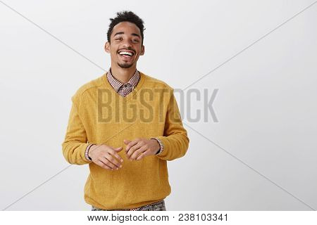 Funny friend tells hilarious jokes. Indoor shot of pleased happy african-american in stylish outfit smiling broadly and gesturing over chest during conversation, having nice talk with coworker. Emotions concept poster