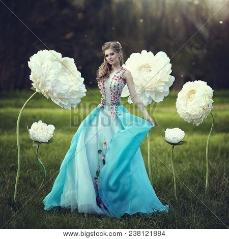 A Beautiful Girl Like Thumbelina In A Blue Fluffy Dress Near Giant Flowers. Blonde With Huge Fairy F
