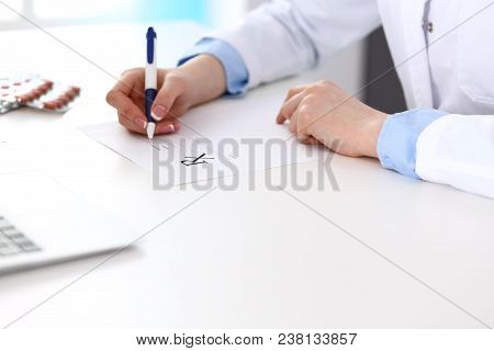Female Doctor Filling Up Prescription Form While Sitting At The Desk In Hospital Closeup. Physician