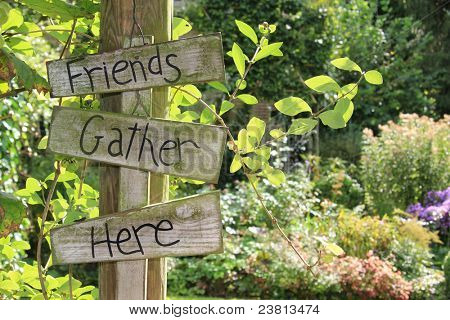 Summer garden welcome sign on a post.