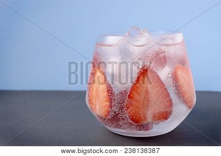 Strawberries In Sparkling Water On The Blue Background. Glass Of Strawberry Summer Water. Cold Fruit