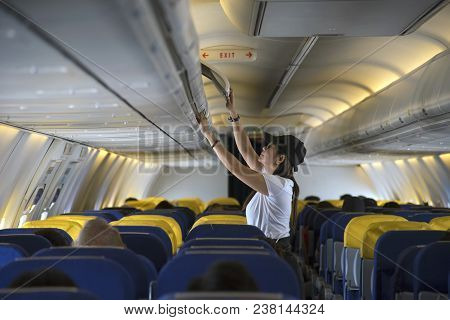Traveller Woman Open Overhead Locker; Her Hand Luggage Into Overhead Locker On Airplane.