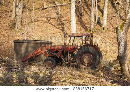 Red Old Tractor Abandoned In A Forest In The Autumn With Leaves On The Ground