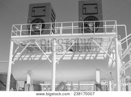 The Tank With Water And A Ladder. Oil Refinery. Equipment For Primary Oil Refining. Water Cooling To
